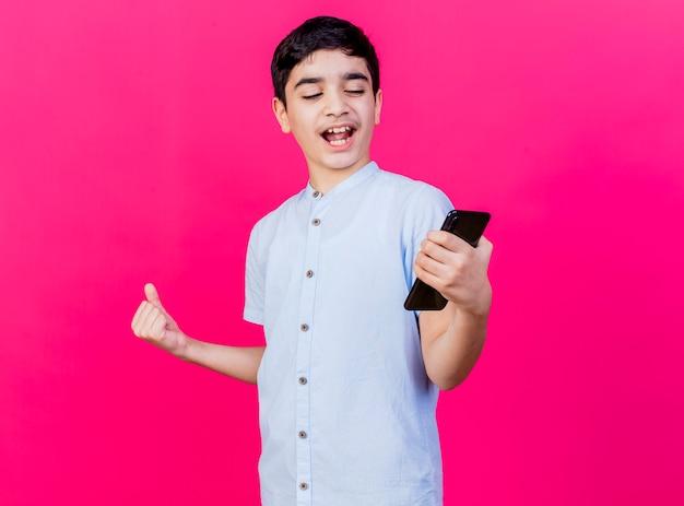 Blije jonge kaukasische jongen die en mobiele telefoon houdt bekijkt die ja gebaar doet dat op karmozijnrode muur wordt geïsoleerd
