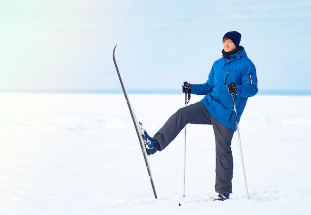 Blije, jonge kerel die in de winter skiet. man langlaufen, winterpret. kopieer de ruimte