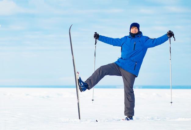Blije, jonge kerel die in de winter skiet. man langlaufen, winterpret.
