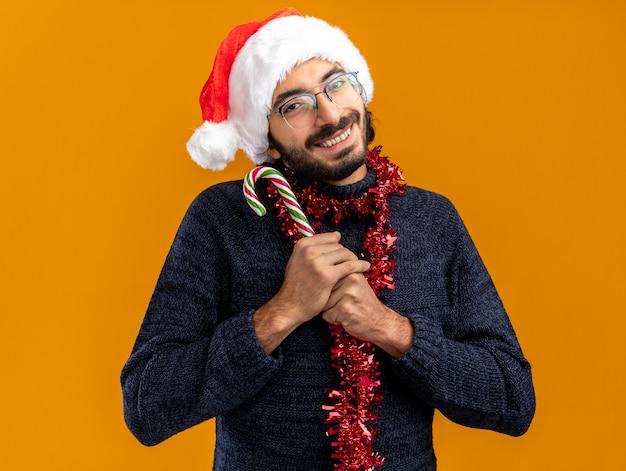 Blije jonge knappe kerel met een kerstmuts met een slinger op de nek met kerstsnoep geïsoleerd op een oranje muur