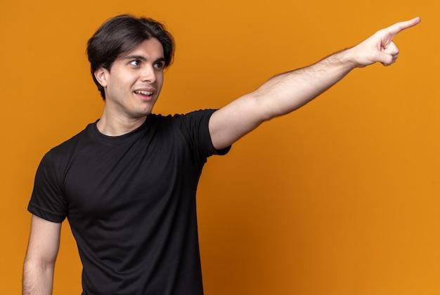 Blije jonge knappe kerel met zwarte t-shirtpunten aan de zijkant geïsoleerd op een oranje muur