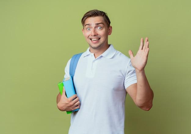 Blije jonge knappe mannelijke student die de boeken van de achterzakholding draagt en hallo gegeven op olijfgroene achtergrond wordt gegeven