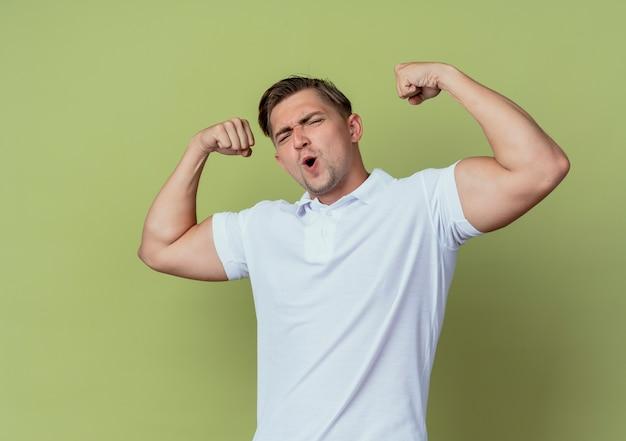 Blije jonge knappe mannelijke student die sterk gebaar doet dat op olijfgroene achtergrond wordt geïsoleerd