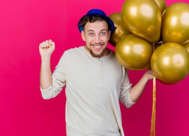 Blije jonge knappe slavische partijkerel die partijhoed draagt die ballons houdt die voorste balde vuist bekijkt die op roze muur wordt geïsoleerd