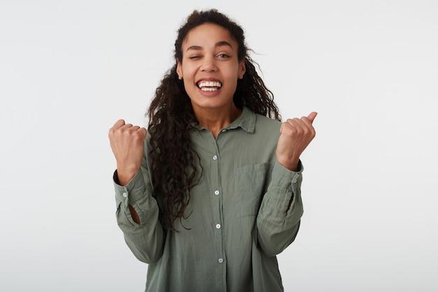 Blije jonge krullende donkerbruine vrouw met donkere huid die gelukkig haar handen opheft en wijd lacht terwijl ze op wit staat in vrijetijdskleding