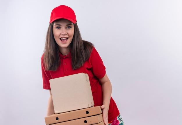Blije jonge leveringsvrouw die rode t-shirt in rood glb draagt die een doos en een pizzadoos op geïsoleerde witte muur houdt