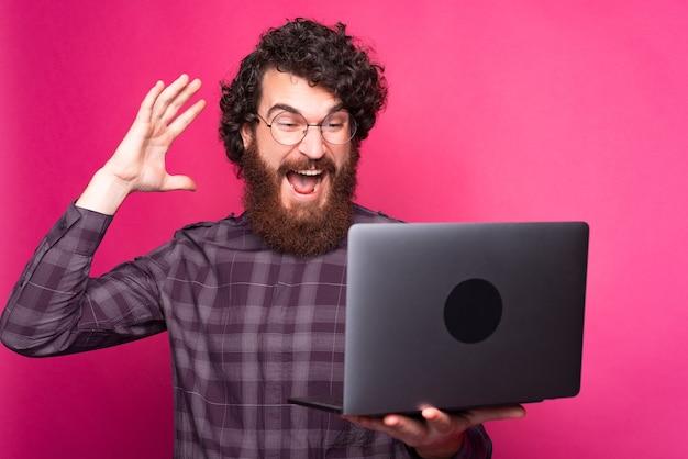 Blije jonge man die een computer houdt die ernaar kijkt opgewonden