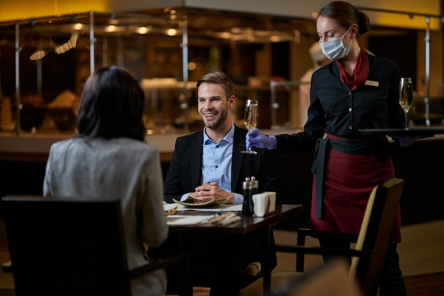 Blije jonge man die een gesprek heeft met een vrouw aan de eettafel terwijl de serveerster glas met alcohol brengt bringing