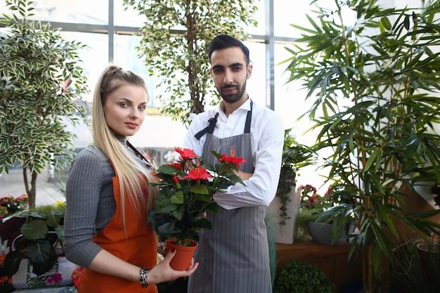 Blije jonge man en vrouw die in bloemenwinkel werken