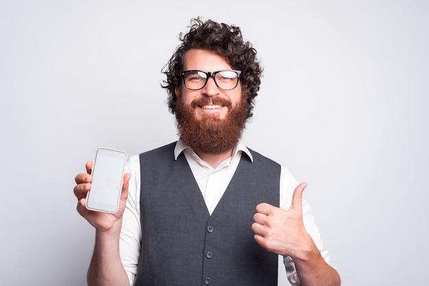 Blije jonge man glimlacht en kijkt naar de camera die een telefoon vasthoudt en een duim toont bij een grijze muur
