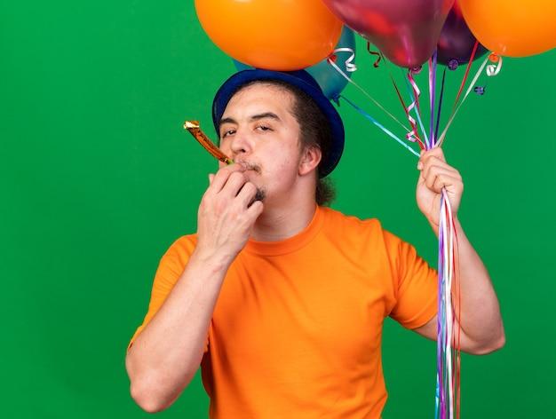 Blije jonge man met feestmuts met ballonnen die feestfluitje blazen