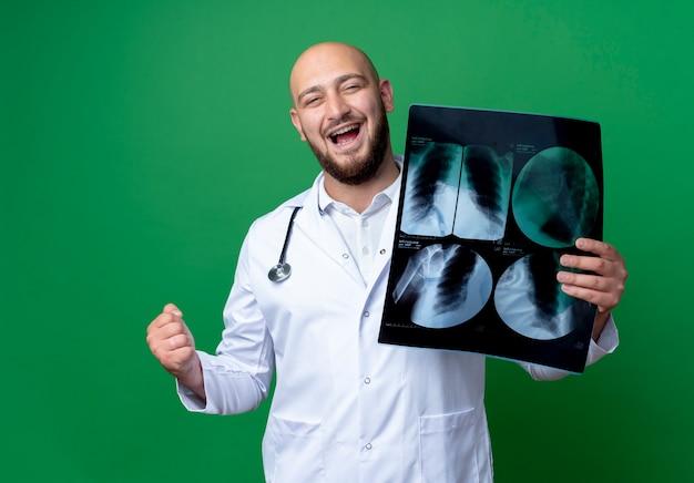 Blije jonge mannelijke arts die medische mantel en stethoscoop draagt die x-ray houdt en ja gebaar toont dat op groene achtergrond wordt geïsoleerd
