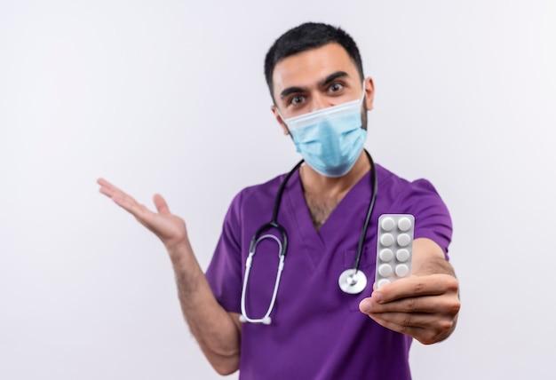 Blije jonge mannelijke arts die purpere chirurgenkleding en een stethoscoop medisch masker draagt dat pillen aan camera standhoudt die hand op geïsoleerde witte muur opheft