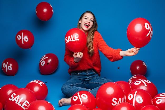 Blije jonge meisjeszitting op de vloer op blauwe muur met rode ballons, verkoop en kortingsconcept
