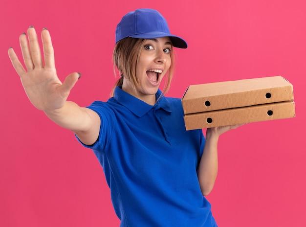 Blije jonge mooie bezorgvrouw in uniforme pizzadozen houden en uitrekkende hand die op roze muur wordt geïsoleerd