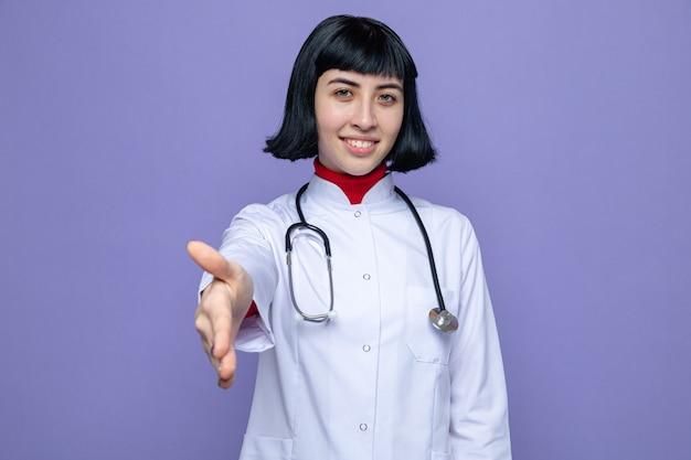 Blije jonge, mooie blanke vrouw in doktersuniform met een stethoscoop die hand uitsteekt?