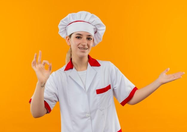 Blije jonge mooie kok in eenvormige chef-kok met tandsteunen die ok teken doen en lege die hand op oranje ruimte tonen tonen