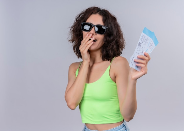 Blije jonge mooie reizigersvrouw die zonnebril draagt en vliegtuigtickets houdt en hand op mond legt op geïsoleerde witte muur met exemplaarruimte