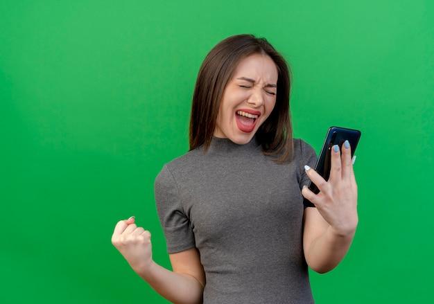 Blije jonge mooie vrouw die mobiele telefoon houdt en ja gebaar met gesloten ogen doet die op groene achtergrond met exemplaarruimte wordt geïsoleerd