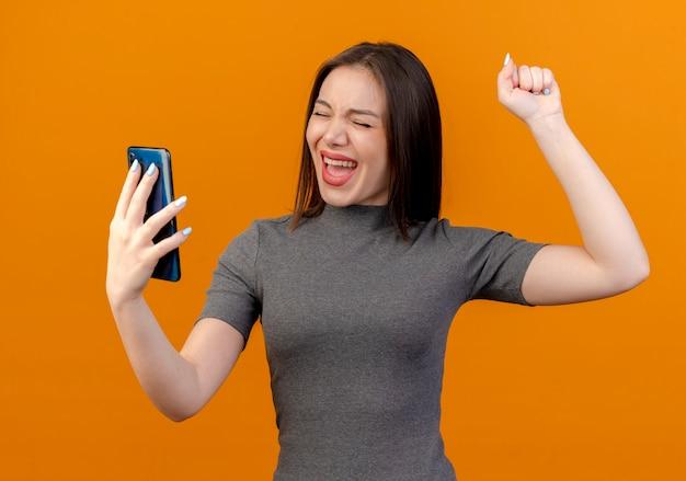 Blije jonge mooie vrouw die mobiele telefoon houdt en vuist met gesloten ogen opheft die op oranje achtergrond worden geïsoleerd