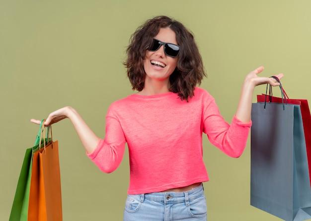 Blije jonge mooie vrouw die zonnebril draagt en kartonnen zakken op geïsoleerde groene muur houdt