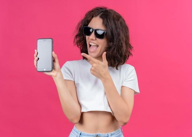 Blije jonge mooie vrouw die zonnebril draagt en mobiele telefoon houdt die op geïsoleerde roze muur met exemplaarruimte richt