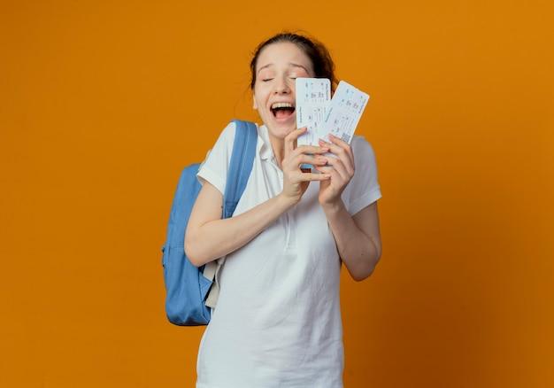 Blije jonge mooie vrouwelijke student die de vliegtuigtickets van de achterzak dragen met gesloten ogen die op oranje achtergrond met exemplaarruimte worden geïsoleerd