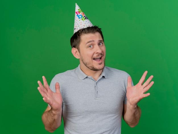 Blije jonge partijkerel die verjaardagsglb spreidende handen draagt die op groen worden geïsoleerd