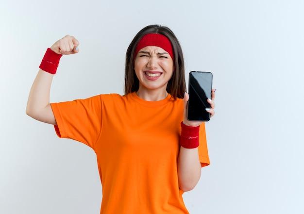 Blije jonge sportieve vrouw die hoofdband en polsbandjes draagt die mobiele telefoon tonen die sterk gebaar doen dat op witte muur met exemplaarruimte wordt geïsoleerd