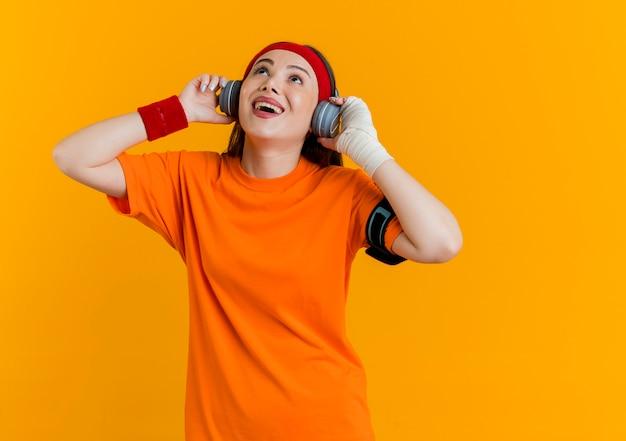 Blije jonge sportieve vrouw die hoofdband en polsbandjes en hoofdtelefoons draagt