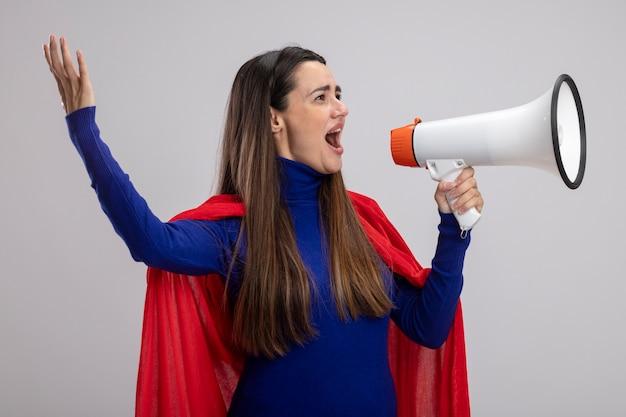 Blije jonge superheld meisje kijken kant spreekt op luidspreker verhogen hand geïsoleerd op een witte achtergrond