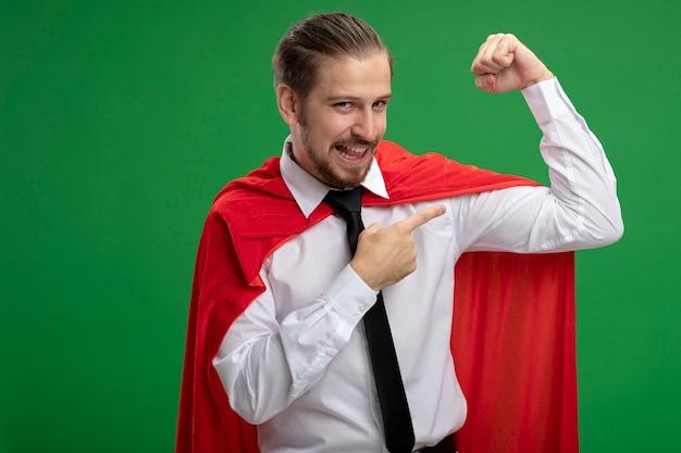 Blije jonge superheldenkerel die sterk gebaar toont dat op groen wordt geïsoleerd