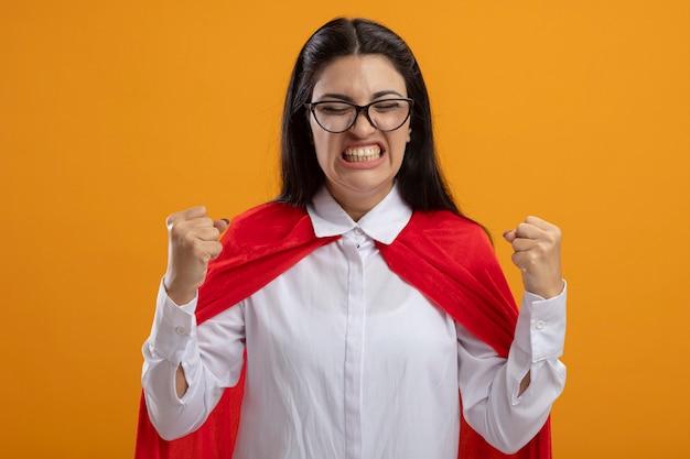 Blije jonge supervrouw die glazen draagt die ja gebaar met gesloten ogen doen die op oranje muur wordt geïsoleerd