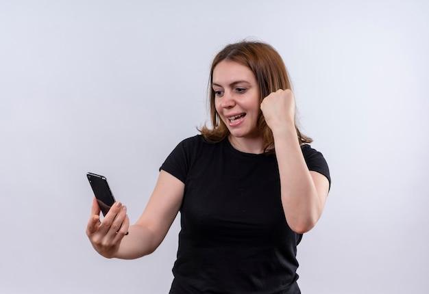 Blije jonge toevallige vrouw die mobiele telefoon houdt die het bekijkt en vuist op geïsoleerde witte ruimte opheft