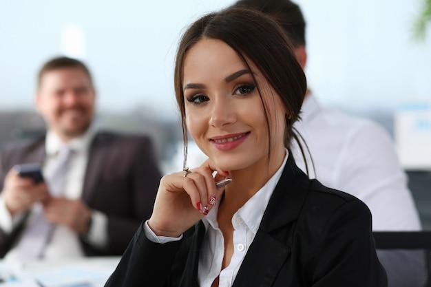 Blije jonge vrouw die met collega's in bureau werkt