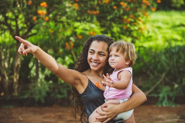 Blije jonge vrouw en klein schattig kind babymeisje wijzen in park