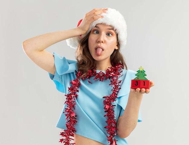 Blije jonge vrouw in blauwe bovenkant en santahoed met klatergoud om haar hals die stuk speelgoed kubussen met kerstmisdatum tong uitsteekt