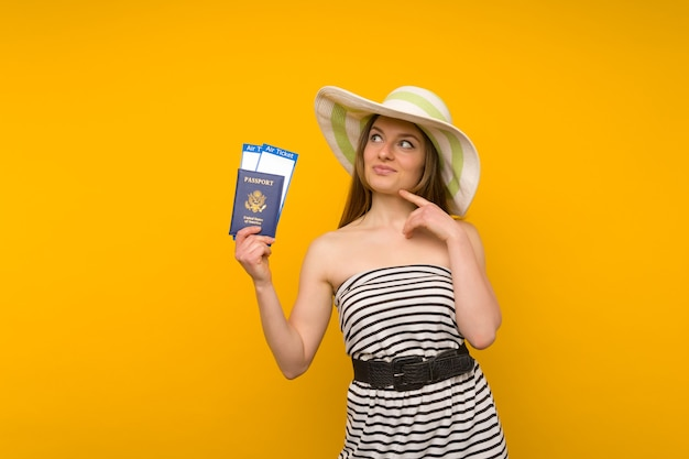 Blije jonge vrouw in een strohoed en een gestreepte jurk houdt vliegtickets met een paspoort op een gele achtergrond.
