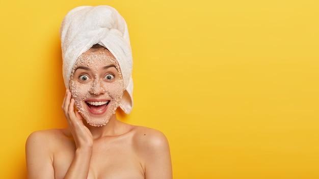 Blije jonge vrouw met afpelmasker, heeft een gevoelige huid, glimlacht breed, toont witte tanden, staart vrolijk, geniet van frisheid op haar teint, draagt een witte handdoek op het hoofd, modellen indoor shirtless