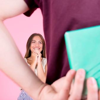 Blije jonge vrouw op zoek man verbergen geschenk in de hand
