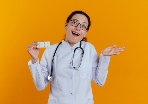 Blije jonge vrouwelijke arts die medische robe en stethoscoop met glazen draagt die pillen houdt en geïsoleerde handen uitspreidt