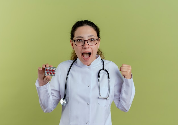 Blije jonge vrouwelijke arts die medische robe en stethoscoop met glazen draagt die pillen houdt en ja geïsoleerd gebaar toont