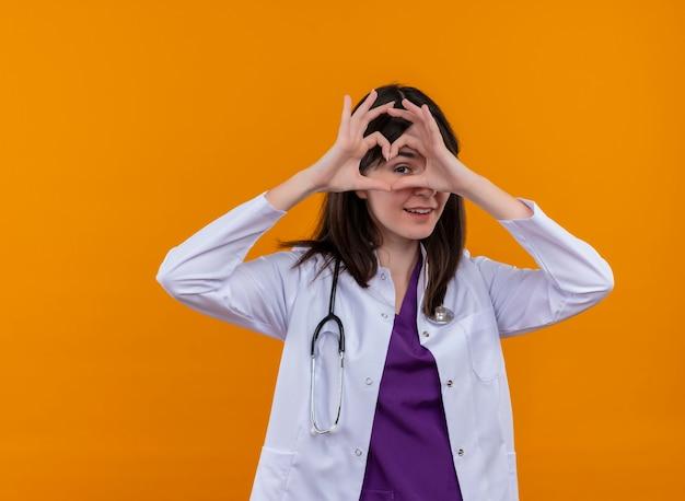 Blije jonge vrouwelijke arts in medisch kleed met het hart van stethoscoopgebaren met beide handen op geïsoleerde oranje achtergrond met exemplaarruimte