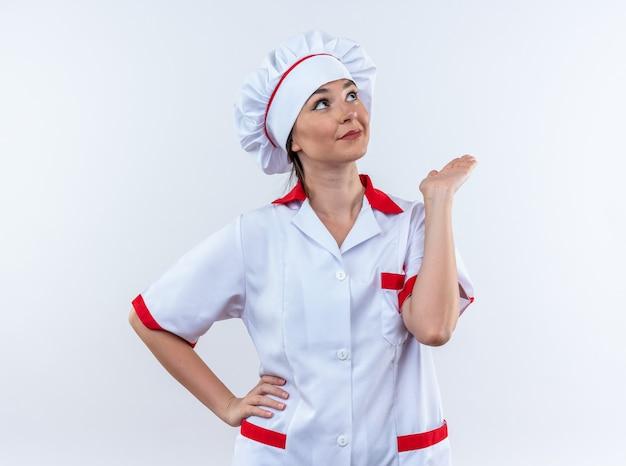 Blije jonge vrouwelijke kok die chef-kok uniform draagt die hand uitspreidt die op witte achtergrond wordt geïsoleerd