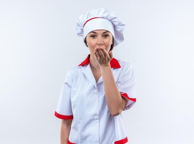 Blije jonge vrouwelijke kok die chef-kok uniform draagt ??die kusgebaar toont dat op witte achtergrond wordt geïsoleerd
