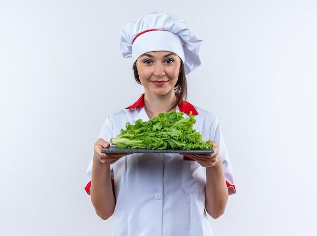 Blije jonge vrouwelijke kok die chef-kok uniform draagt en salade houdt op snijplank geïsoleerd op een witte muur