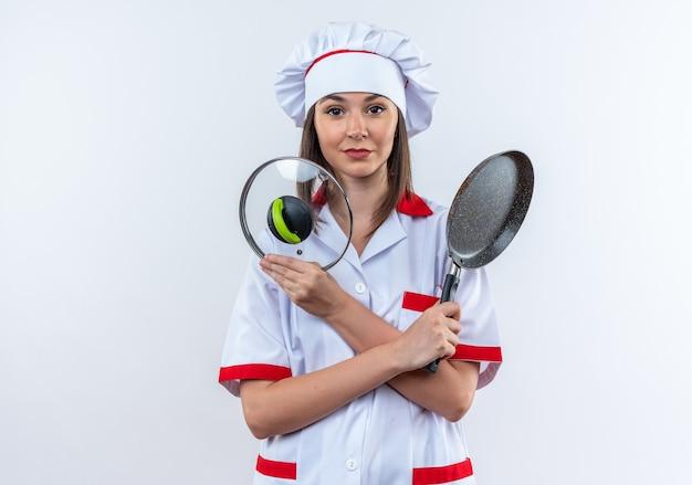 Blije jonge vrouwelijke kok die een chef-kok uniform draagt en een koekenpan met deksel kruist die op een witte achtergrond wordt geïsoleerd