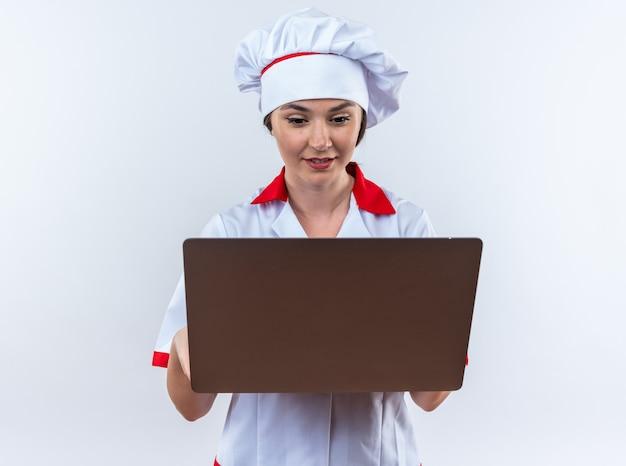 Blije jonge vrouwelijke kok die een chef-kok uniform draagt en naar een laptop kijkt die op een witte muur is geïsoleerd