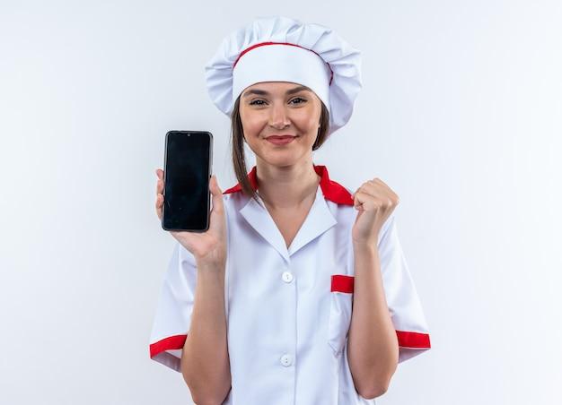 Blije jonge vrouwelijke kok die een chef-kok uniform draagt met een telefoon die ja gebaar toont geïsoleerd op een witte achtergrond