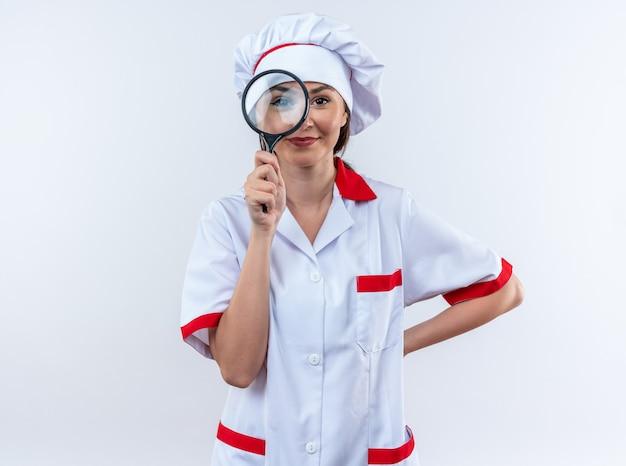 Blije jonge vrouwelijke kok die een uniform van de chef-kok draagt met een vergrootglas die de hand op de heup legt die op een witte muur wordt geïsoleerd